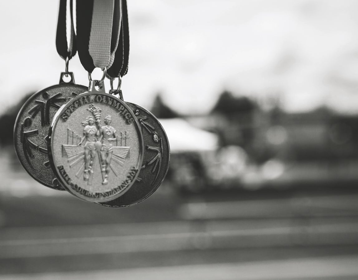 Black and white photo of three hanging medals
