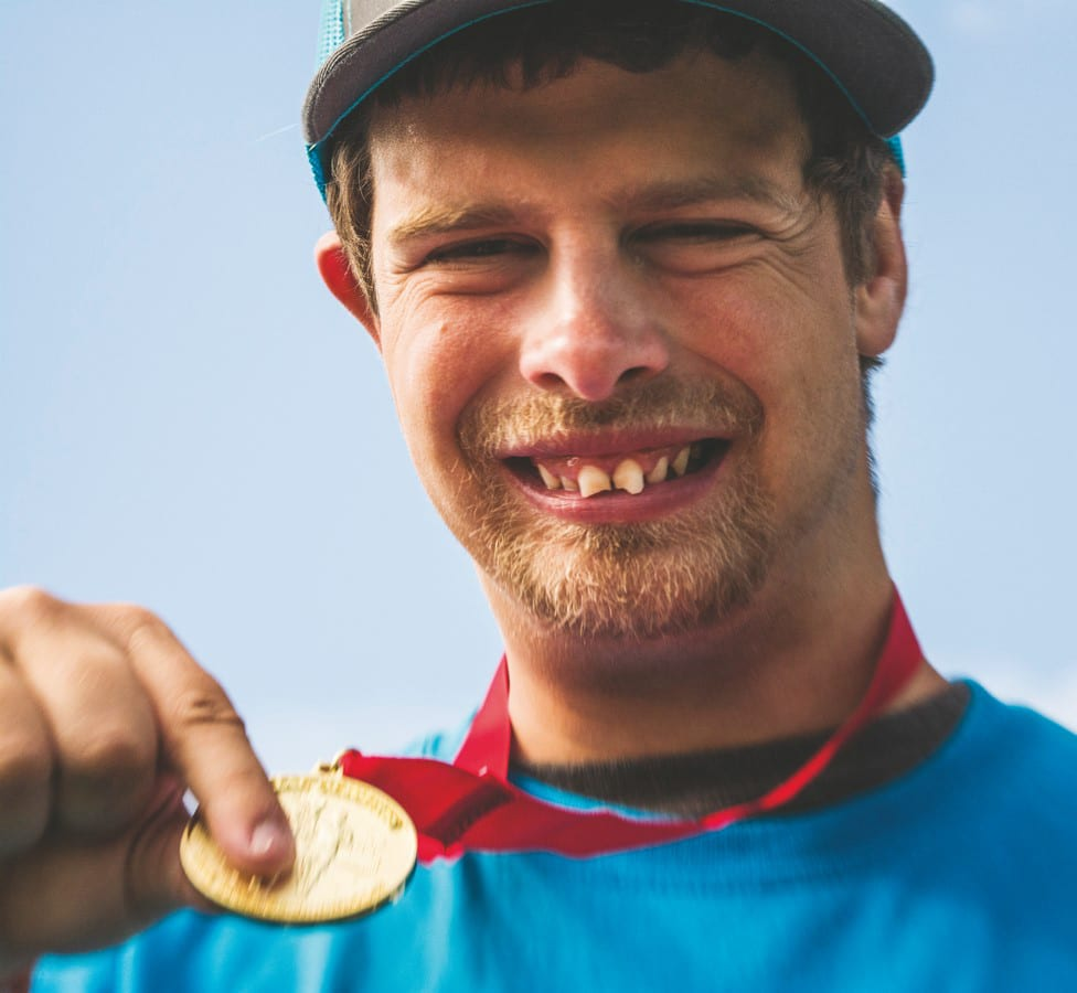 An athlete smiles at the camera while holding their medal up