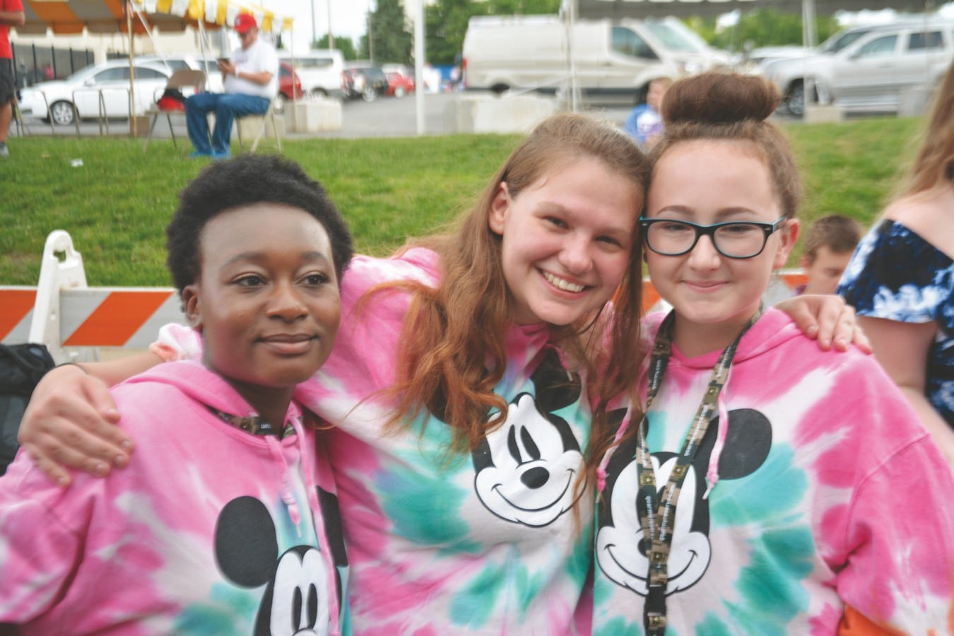 Three athletes in matching tie-dye hoodies pose for a photo with smiles on their faces