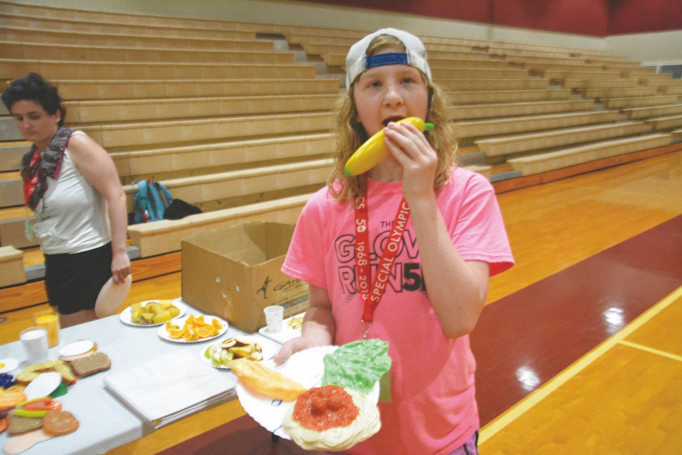 An athlete holds a plate of plastic food and acts as if they are going to eat a plastic banana while looking at the camera