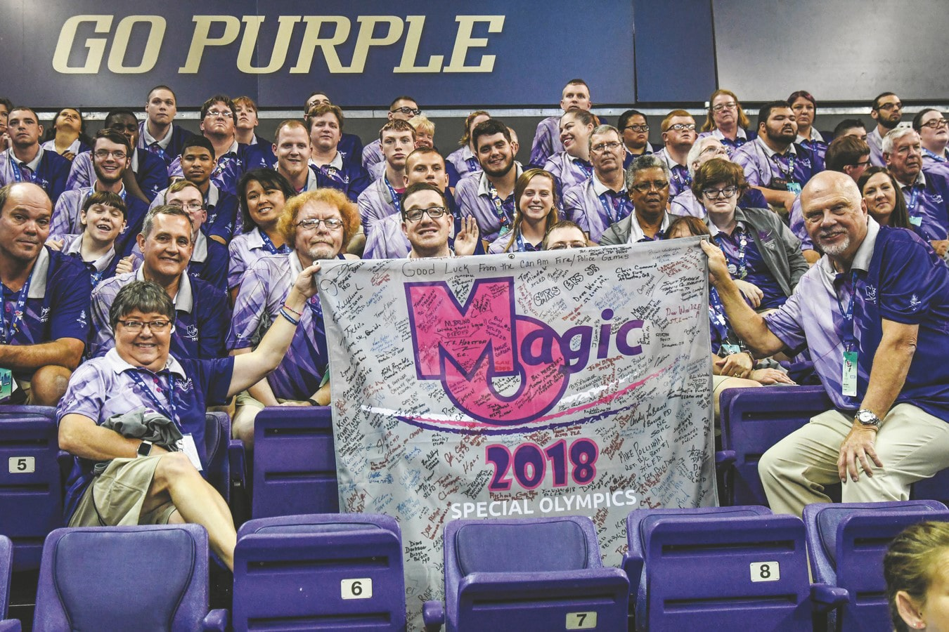 A large group photo of athletes and volunteers from Team Missouri 2018 USA Games holding a MO Magic banner with signatures