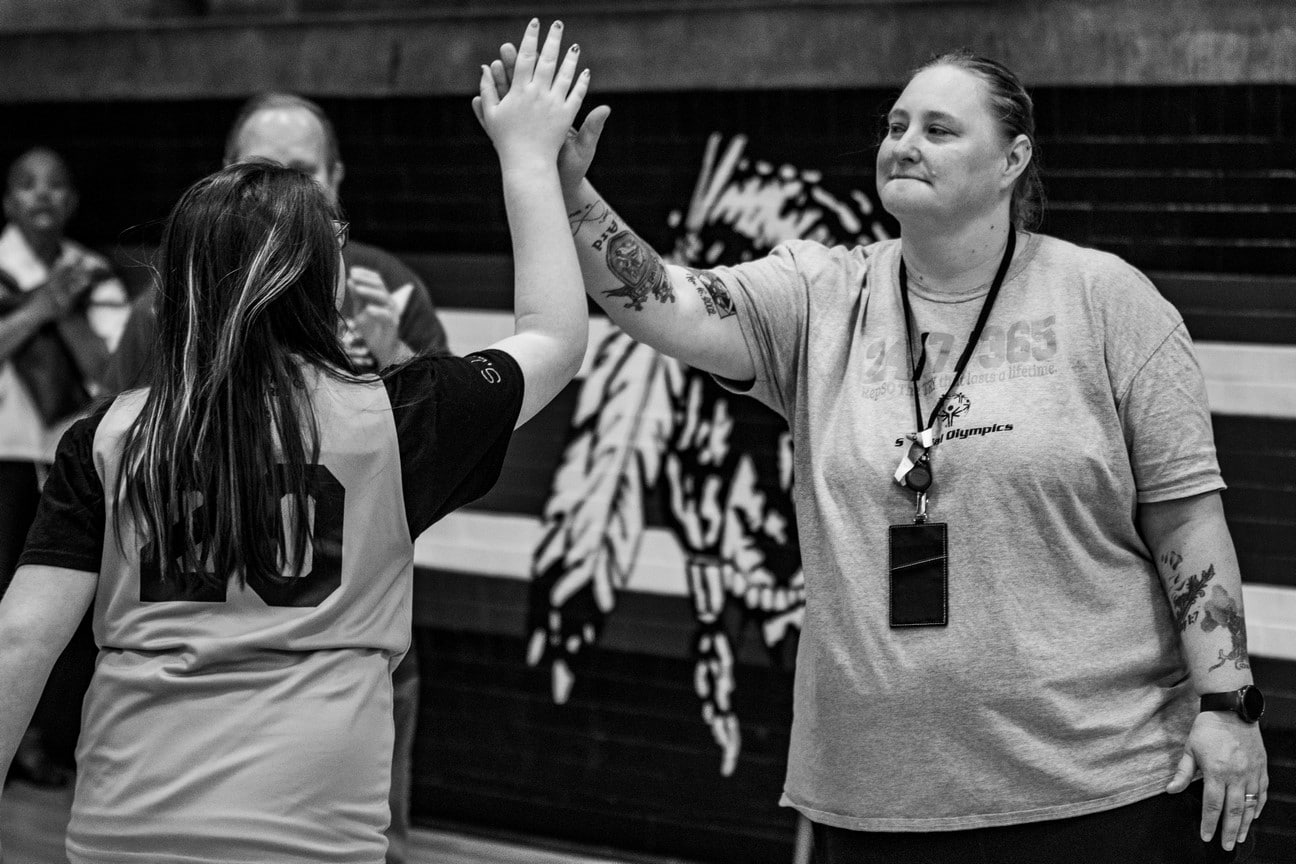 Black and white photo of athlete giving smiling coach a high-five