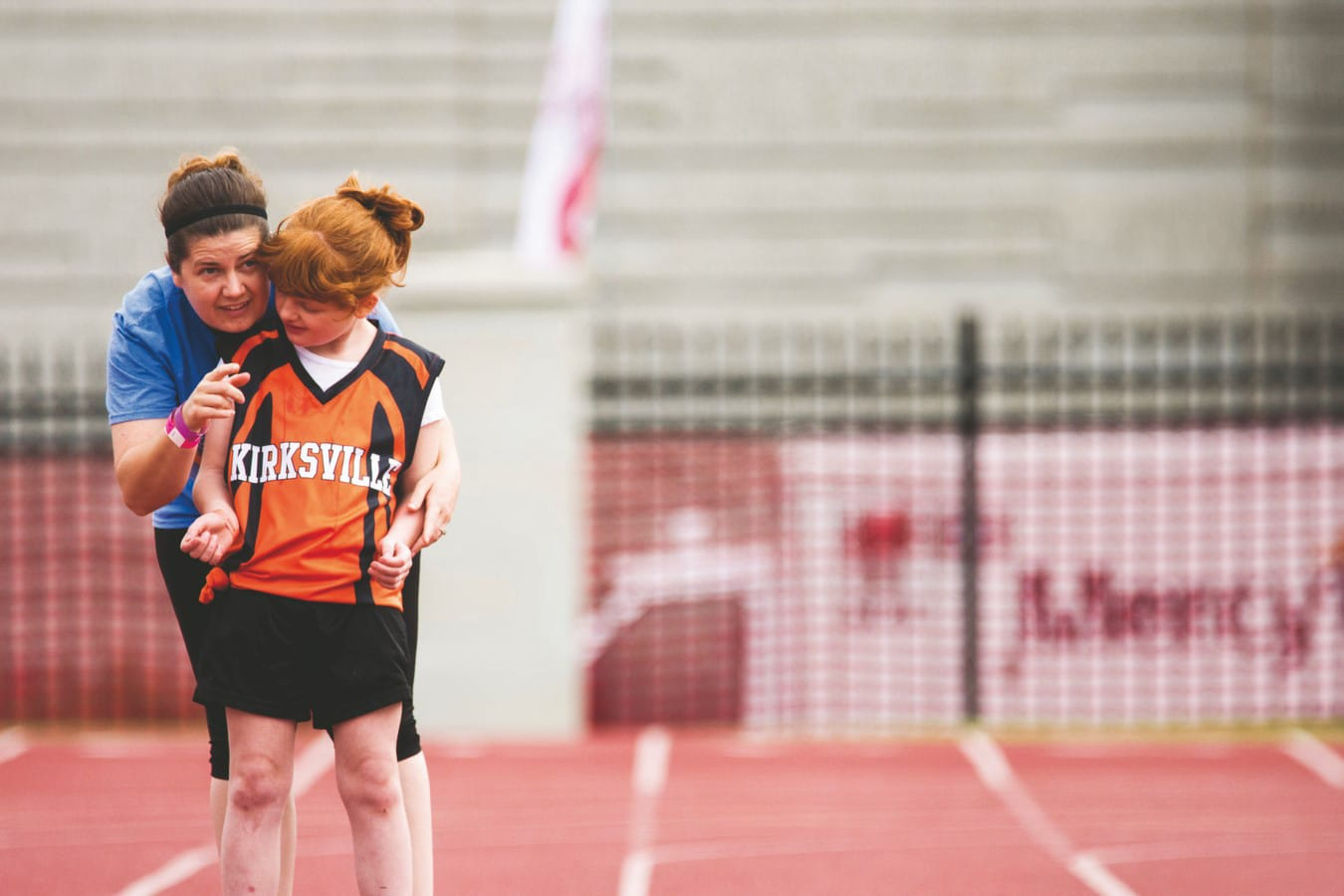 A coach stands behind a young Kirksville athlete on a track and points in the direction they need to run