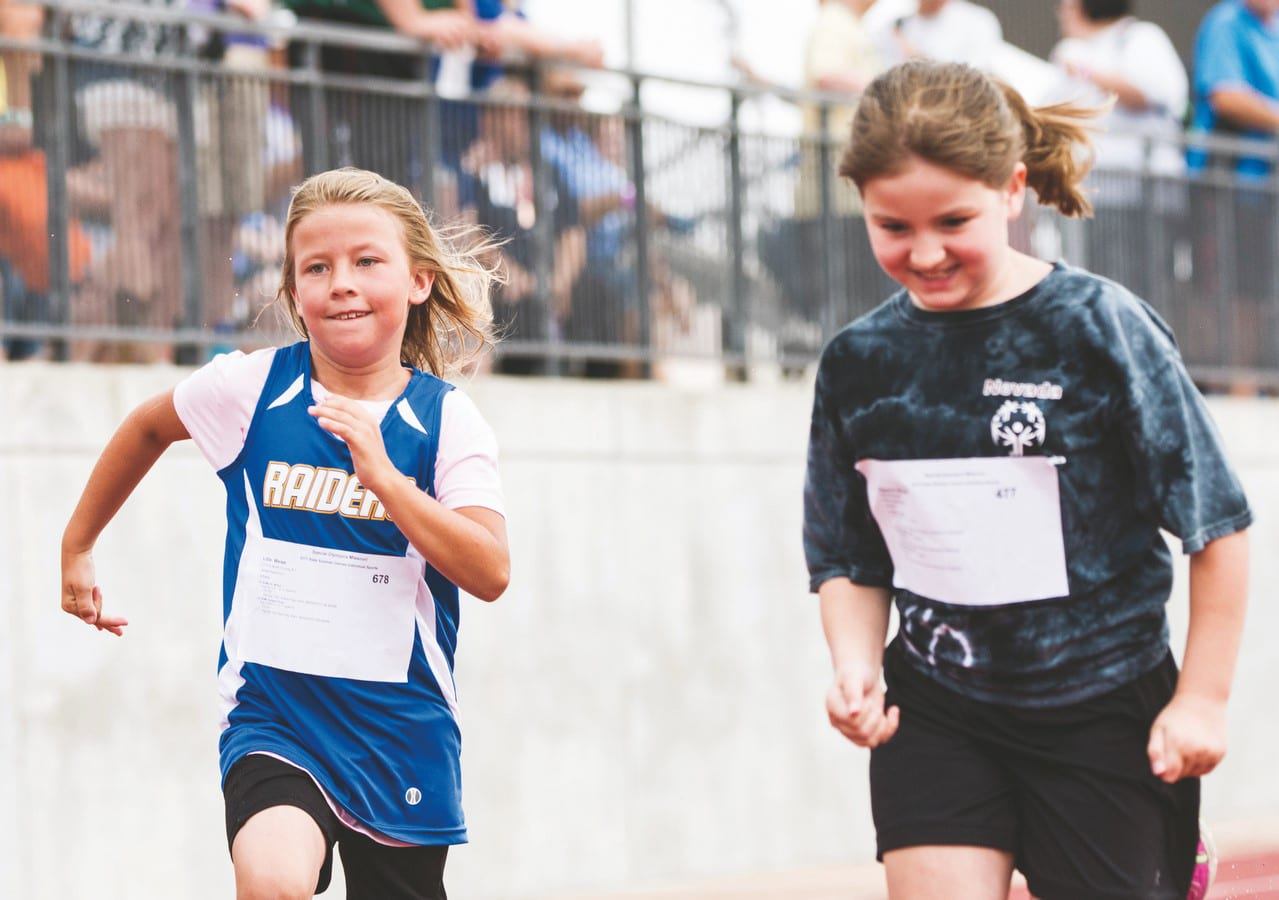 Two young athletes are neck and neck in a track and field race