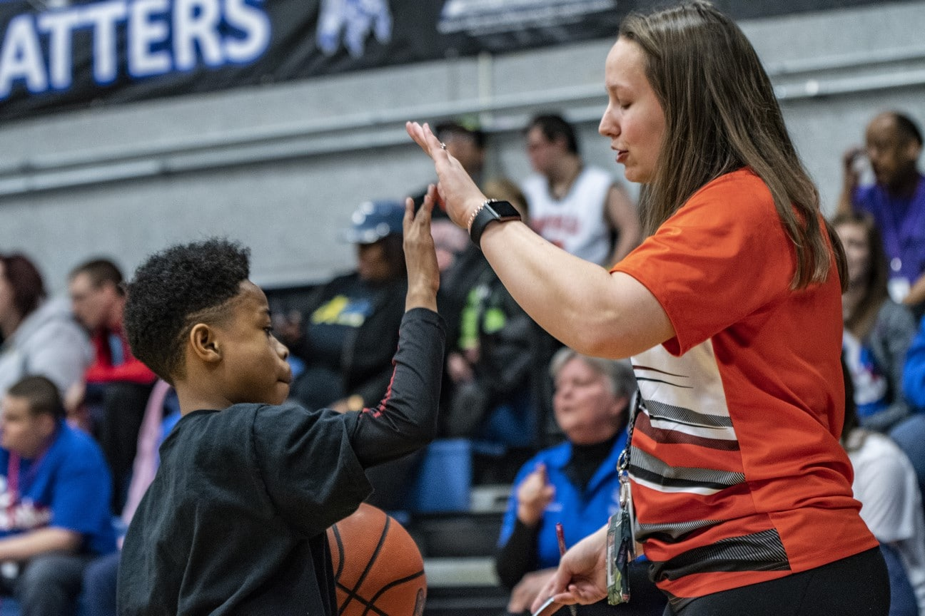 Young athlete holding a basketball gives coach a high-five