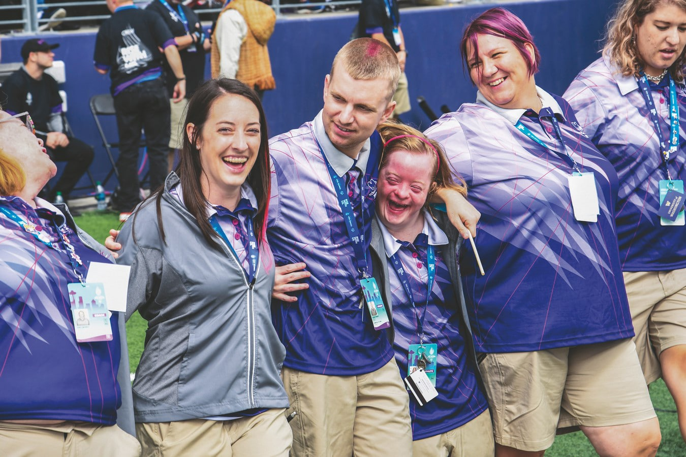 A group of athletes and volunteers stand arm in arm with smiles on their faces