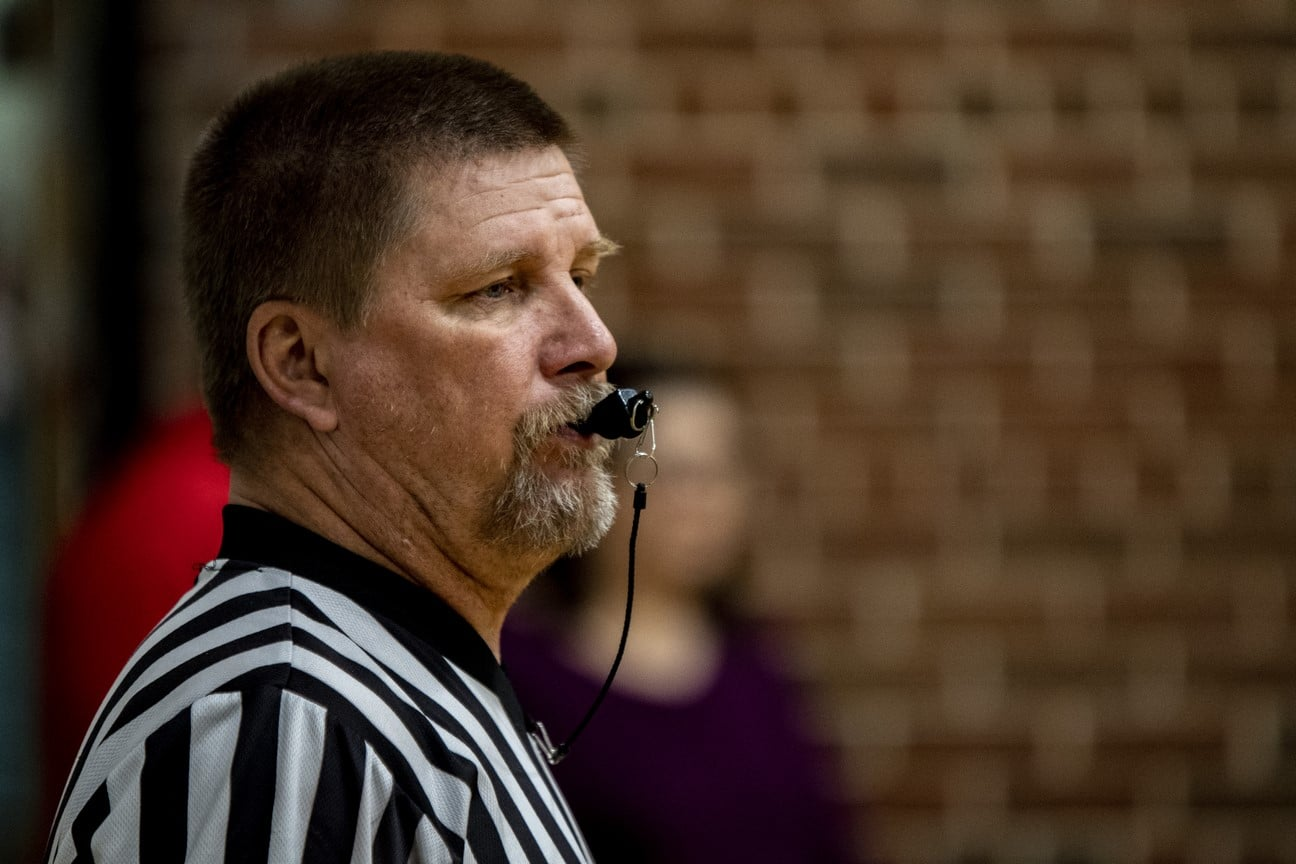 Side profile of referee with a whistle in their mouth