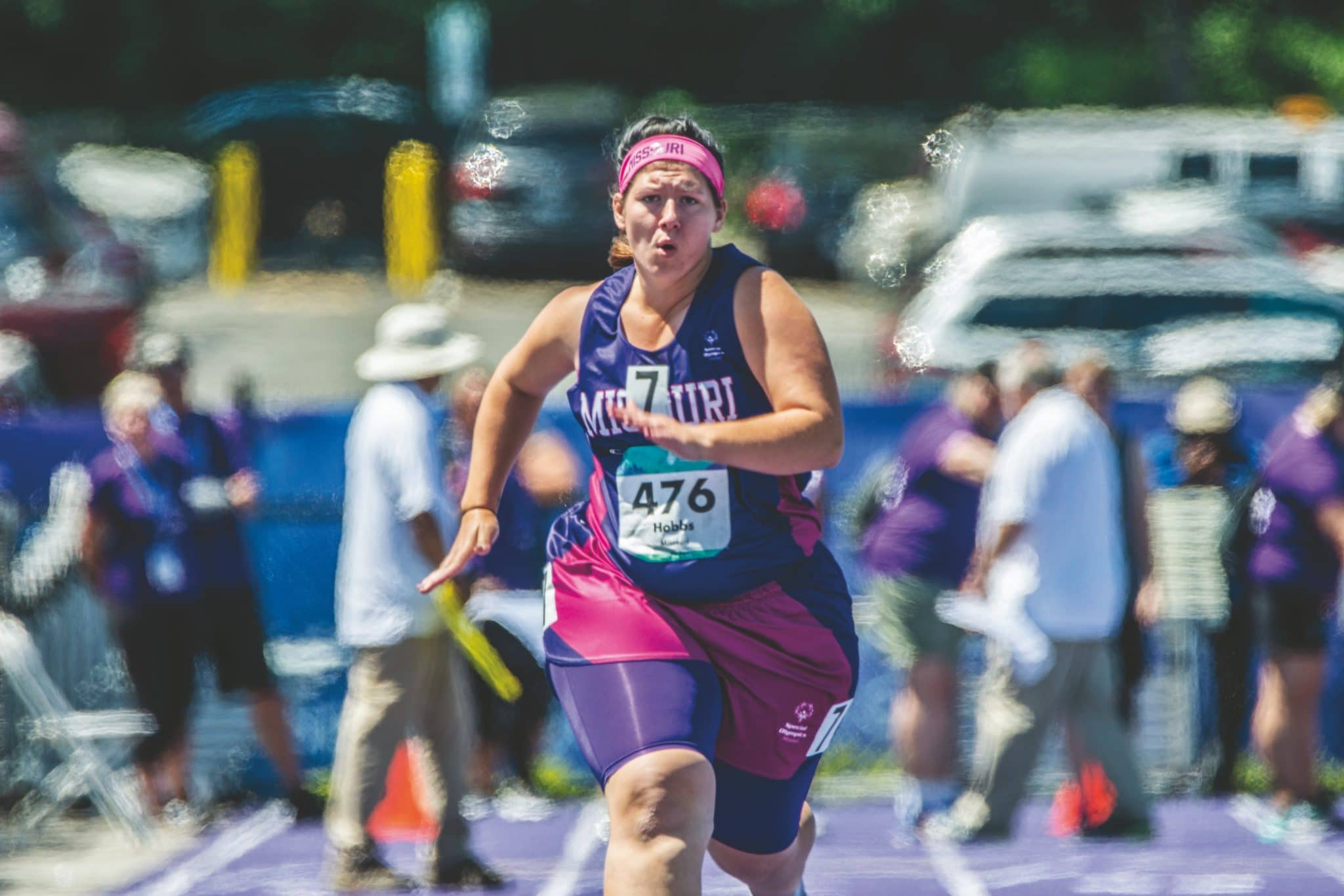 An athlete with a purple and pink Team Missouri uniform runs down the track looking straight ahead into the camera