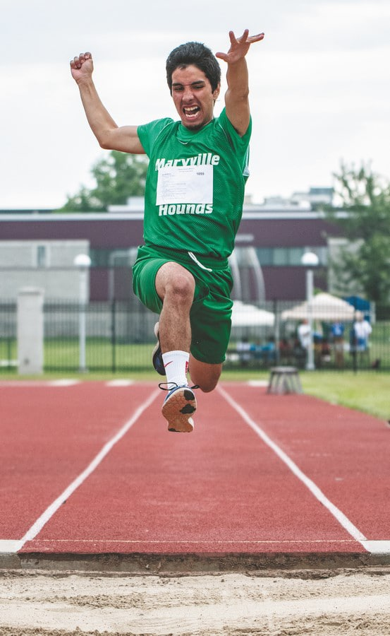 An athlete from Maryville has their arms outstretched as they fly though the air during a long jump competition