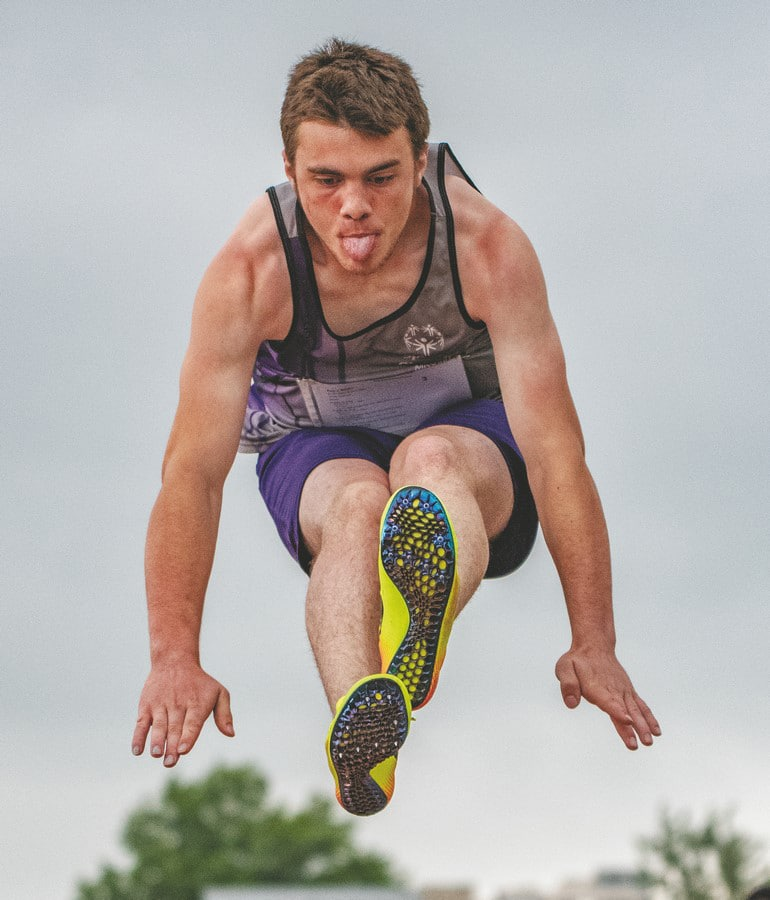 An athlete competing in the long jump flies through the air with their tongue sticking out