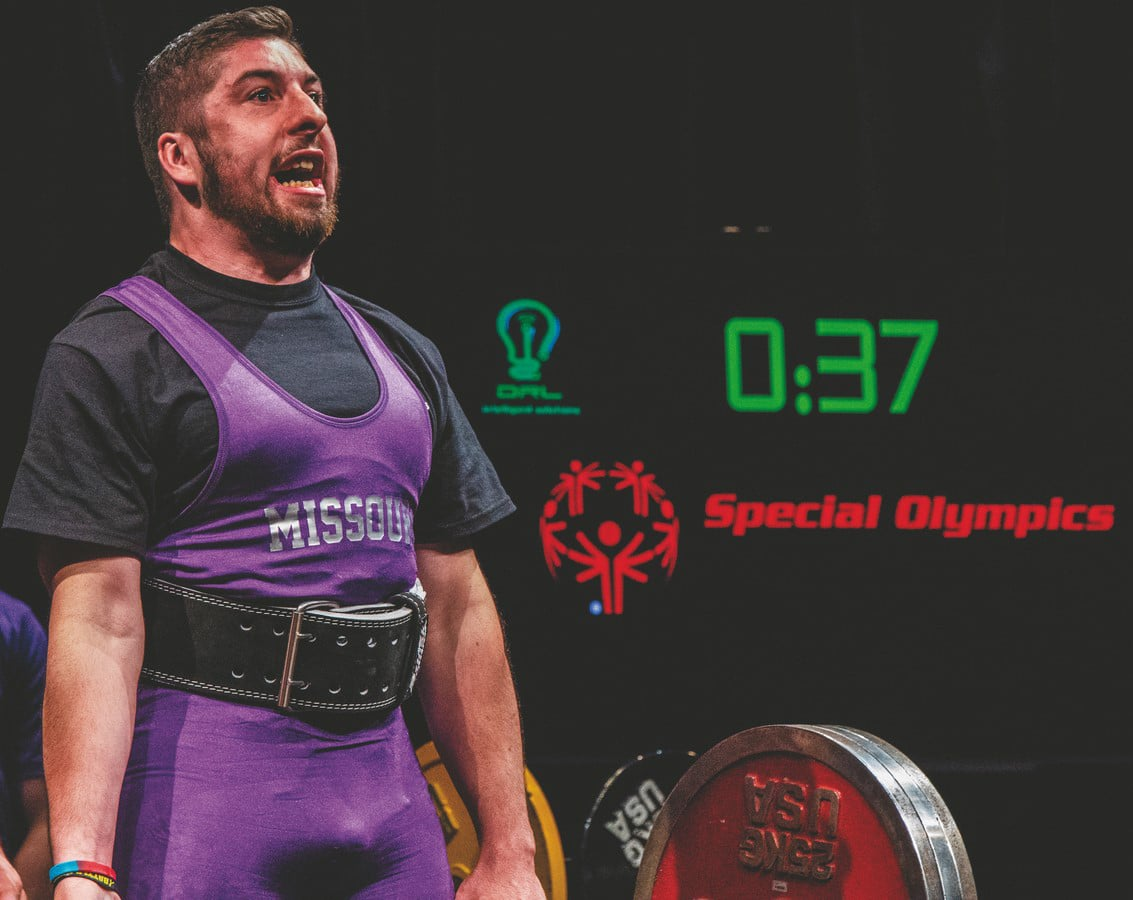 An athlete wearing a purple Team Missouri uniform successfully lifts a large amount of weight with a Special Olympics logo and countdown timer in the background