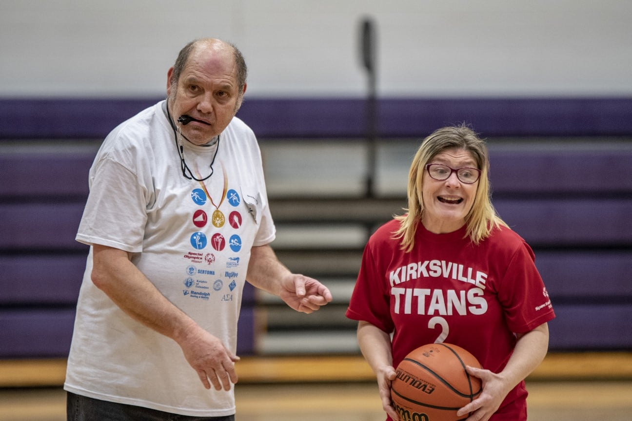 Volunteer with a whistle in their mouth looks to the side as smiling athlete holds a basketball