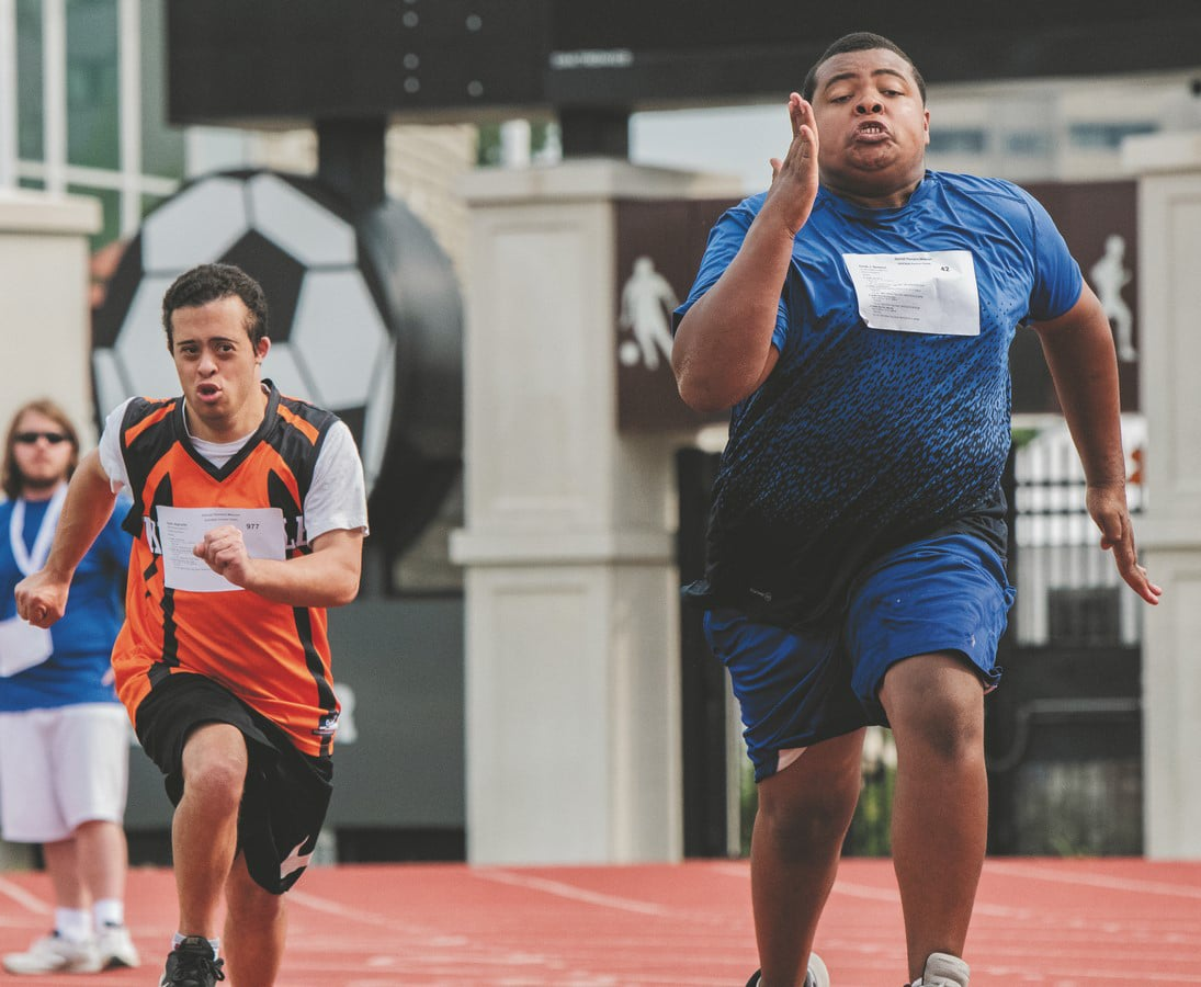 Two athletes with strain on their faces run down the track