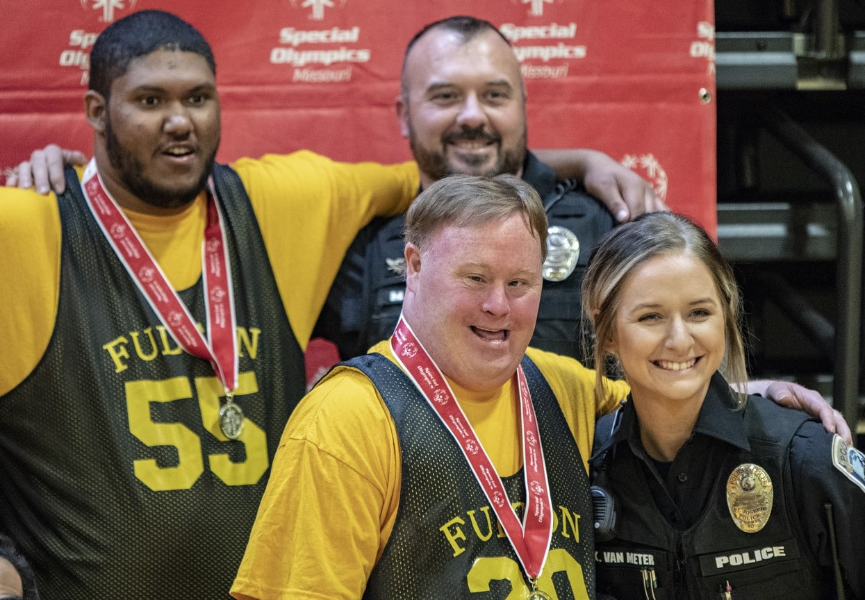 Two smiling athletes with gold medals around their necks pose with two smiling police officers