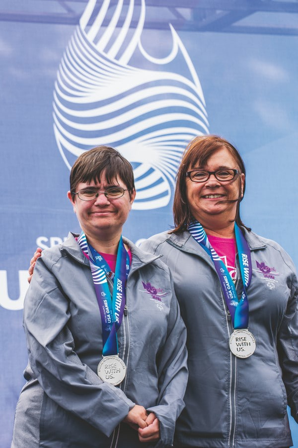 An athlete and Unified Partner, wearing silver medals, look at the camera and smile while on the award stand with a USA Games backdrop behind them