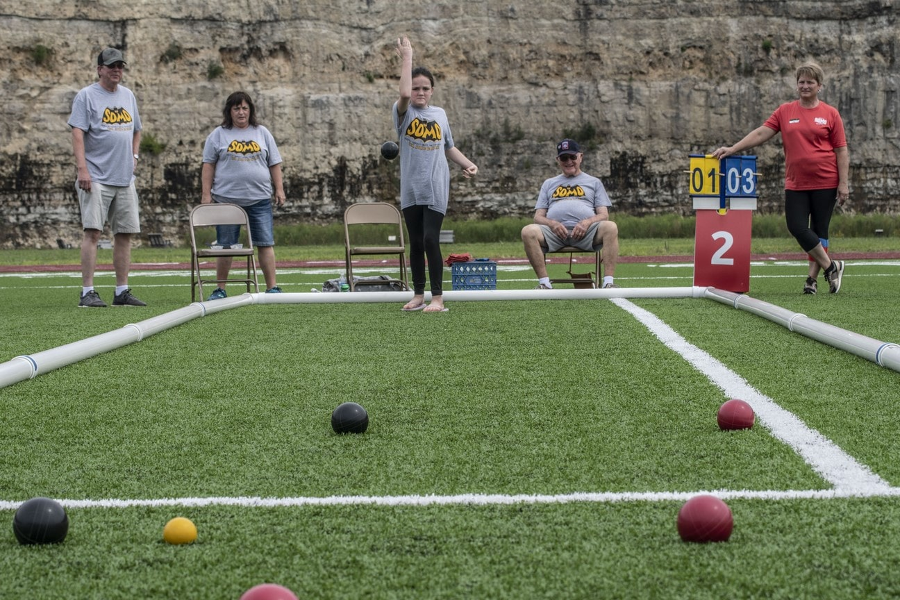 A Young Athlete releases a bocce ball from their hand to roll down the turf field toward the camera