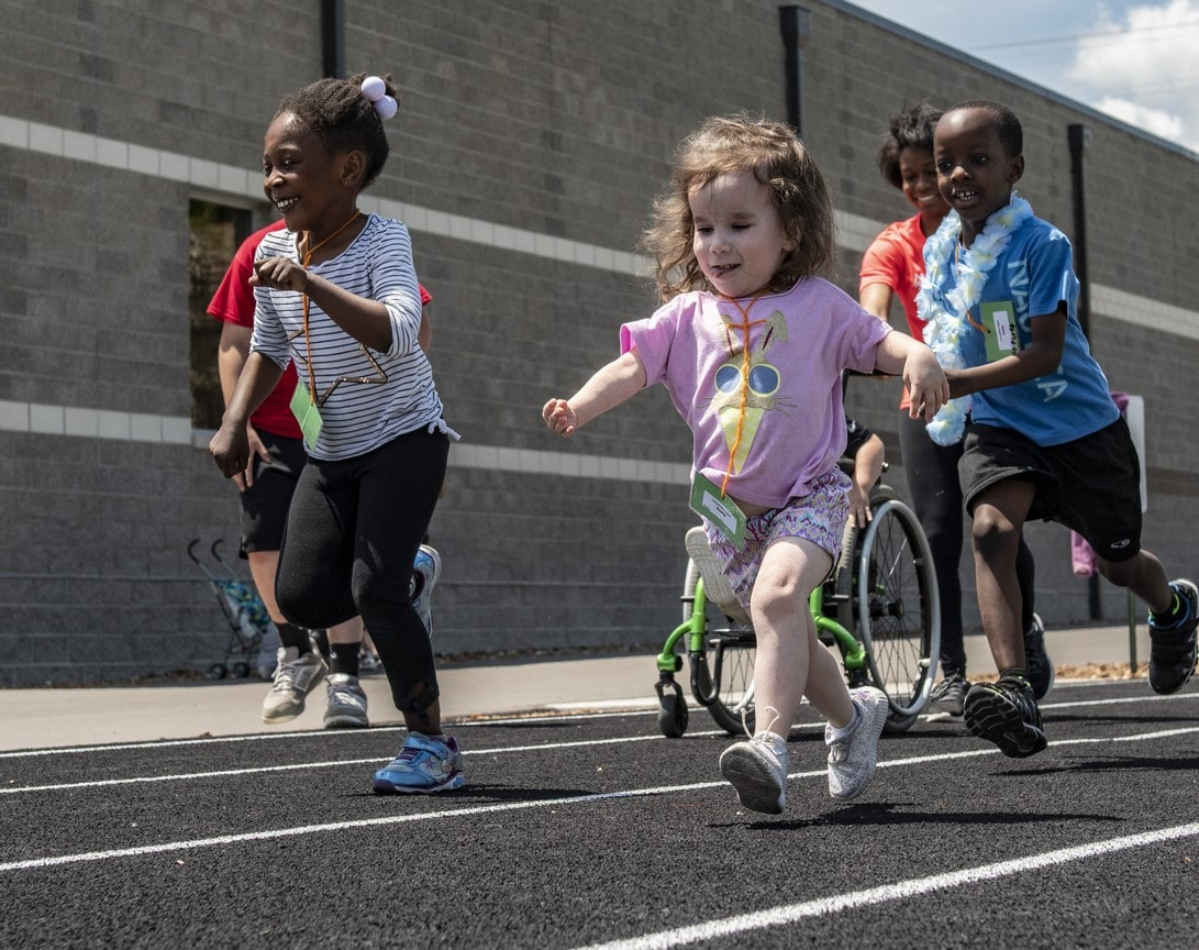 A group of Young Athletes run down the track with smiles on their faces