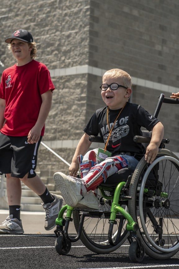 A Young Athlete using a wheelchair streaks down the track at the Training for Life Campus