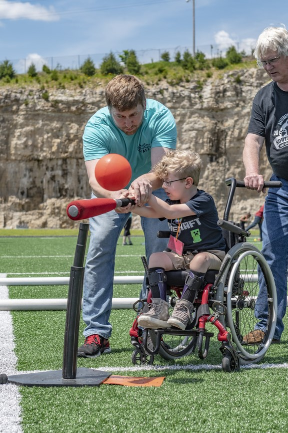 A volunteer helps a Young Athlete using a wheelchair to hit a ball off a tee