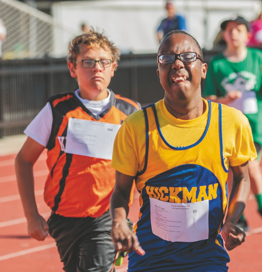 An athlete from Hickman struggles to maintain a lead in a track and field race while another runner tries to track them down
