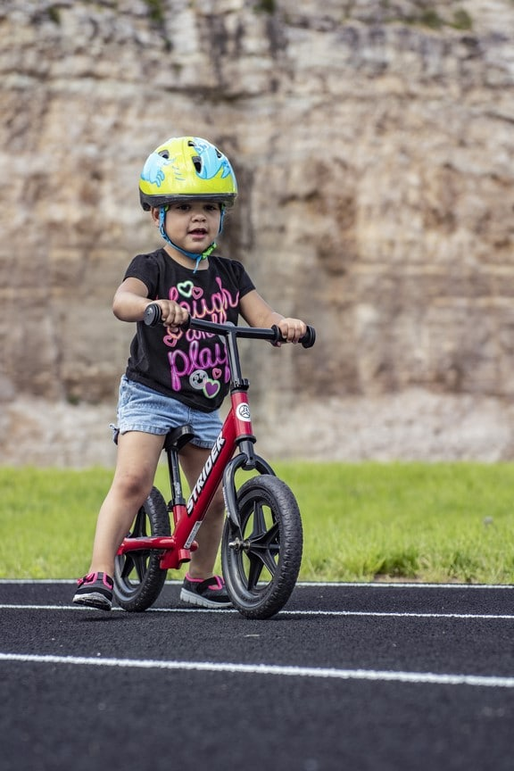 A Young Athlete rides a Strider bicycle on the track at the Training for Life Campus