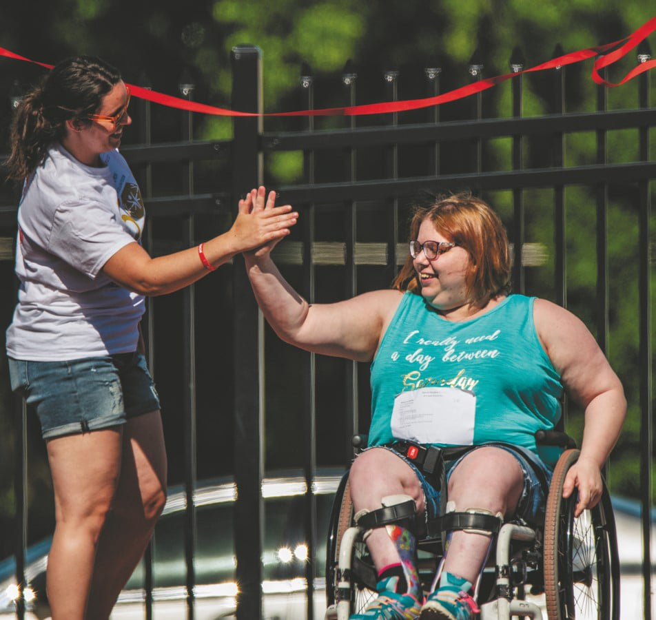 Athlete in a wheelchair smiles while giving the volunteer a high-five