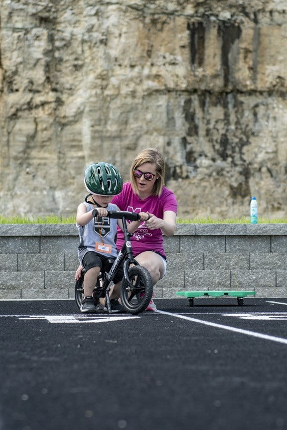 A Young Athletes receives instruction from a volunteer on how to ride a Strider bicycle