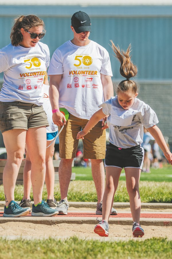 Two volunteers watch as a young athlete jumps into a sand pit