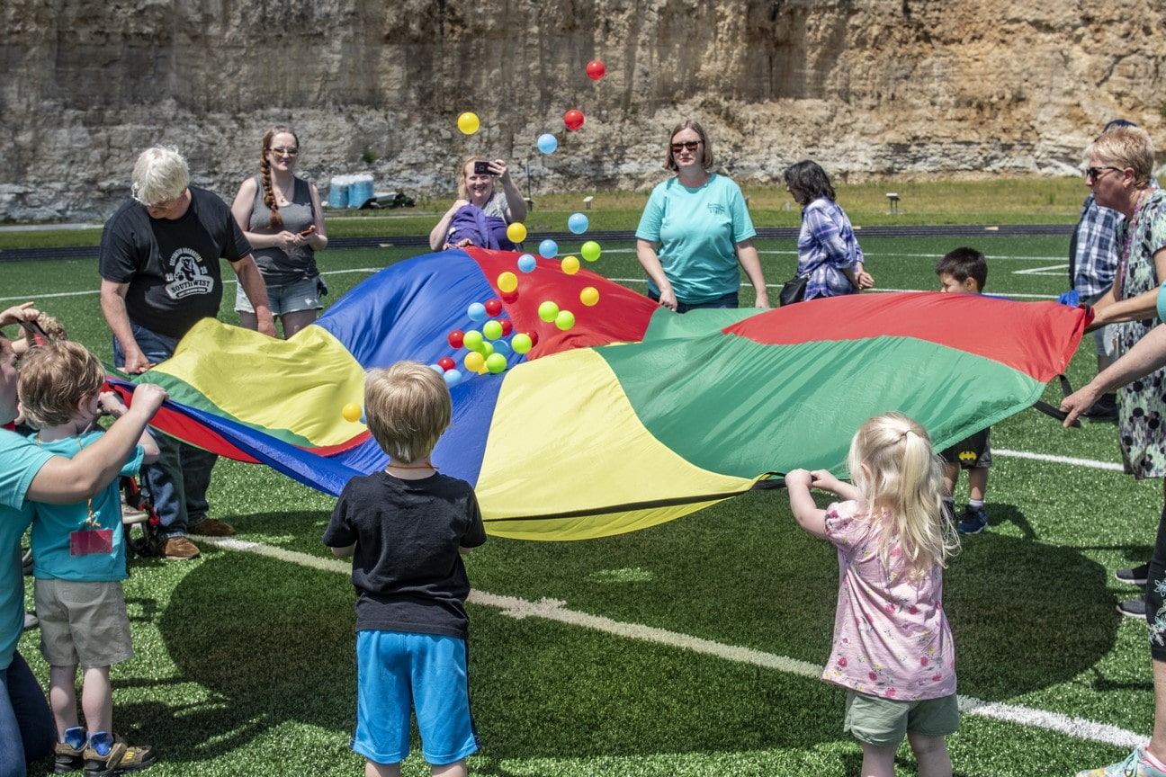 A group of Young Athletes and volunteers use a rainbow parachute to throw balls into the air