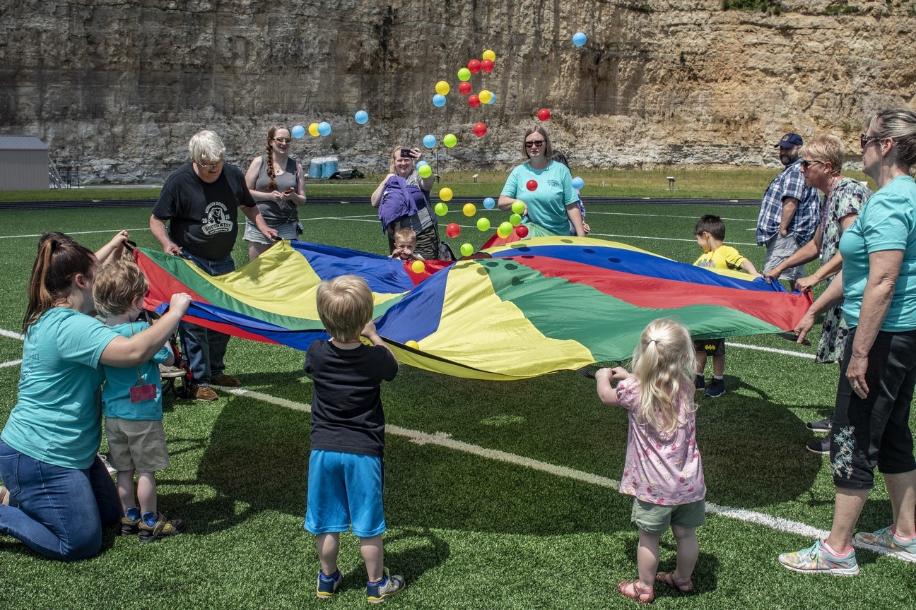Group of young athletes, staff, and volunteers hold edges of a parachute and bounce colorful balls up and down in the middle