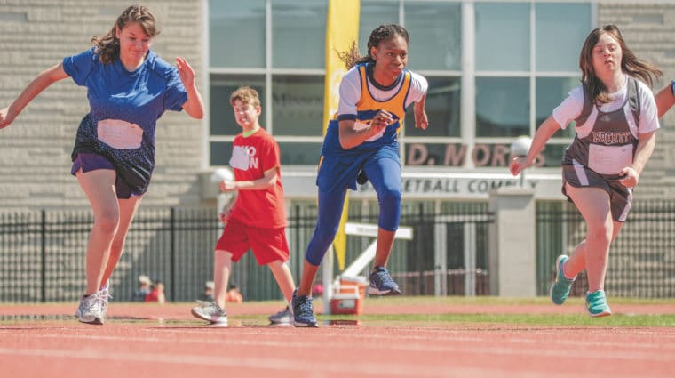 Three athletes break off the starting line during a track and field race