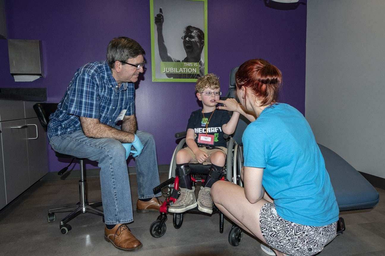 A Young Athlete sits in a wheelchair and receives a dental screening while two adults look on