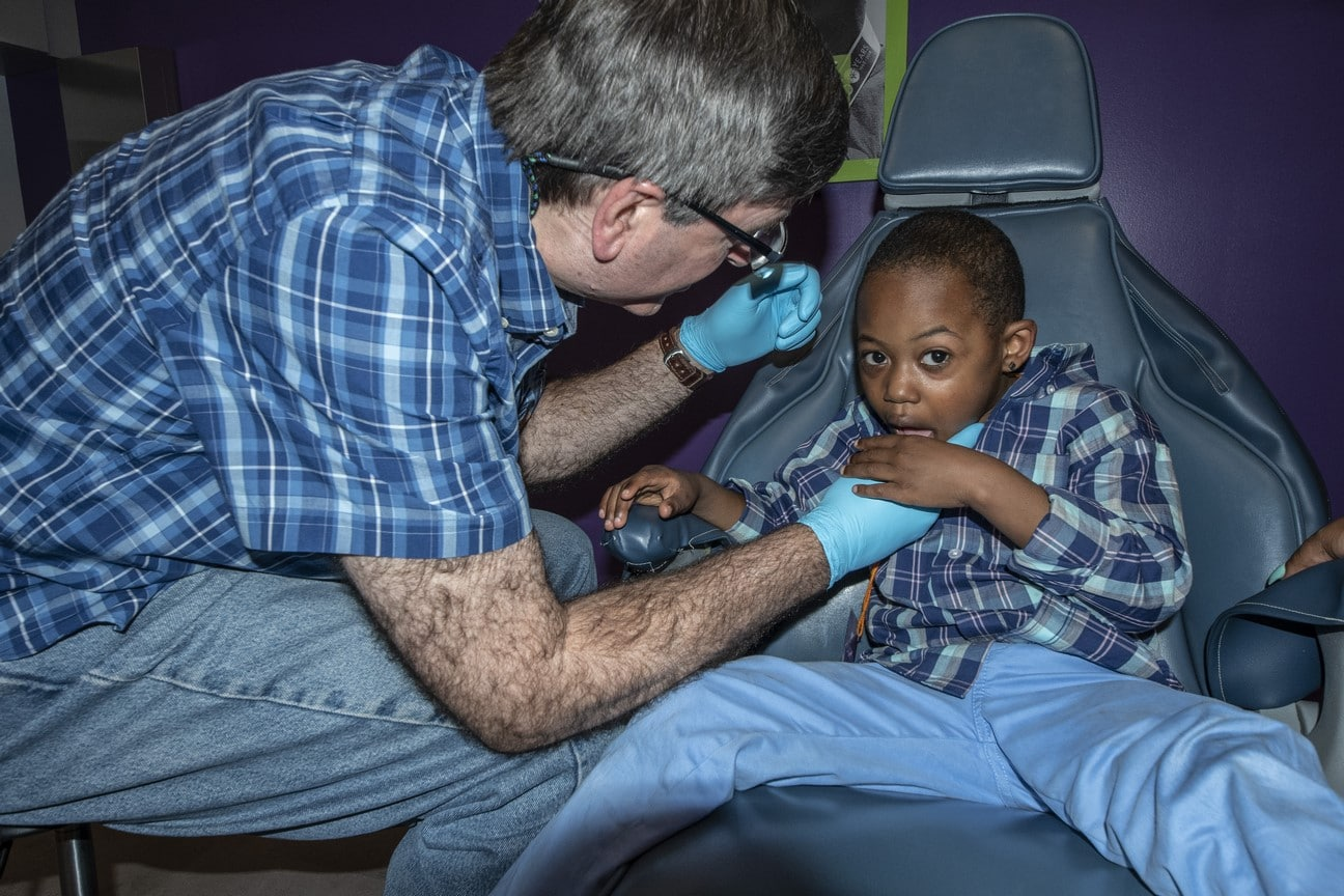 Young athlete sitting in a dental chair gets teeth checked by volunteer dentist