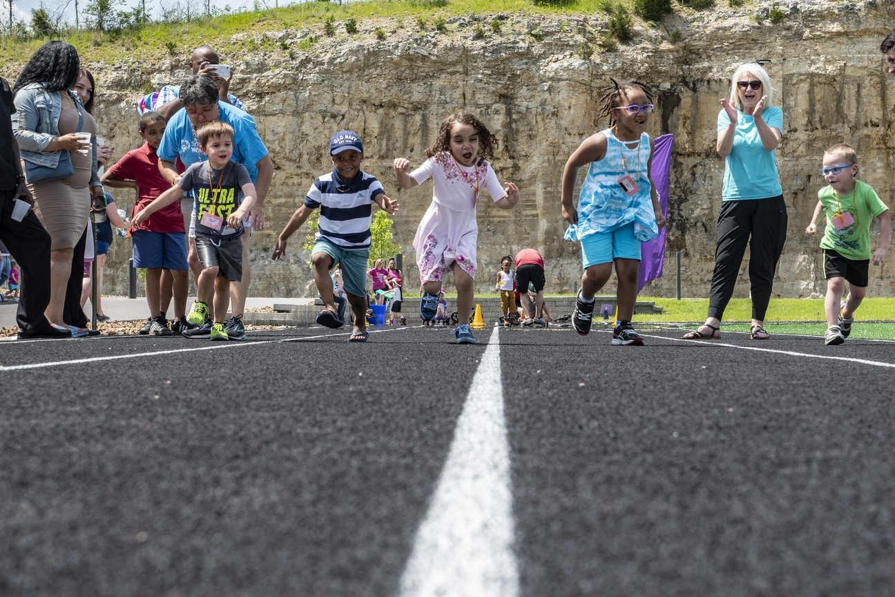 A group of athletes run toward the camera on the track at the Training for Life Campsu