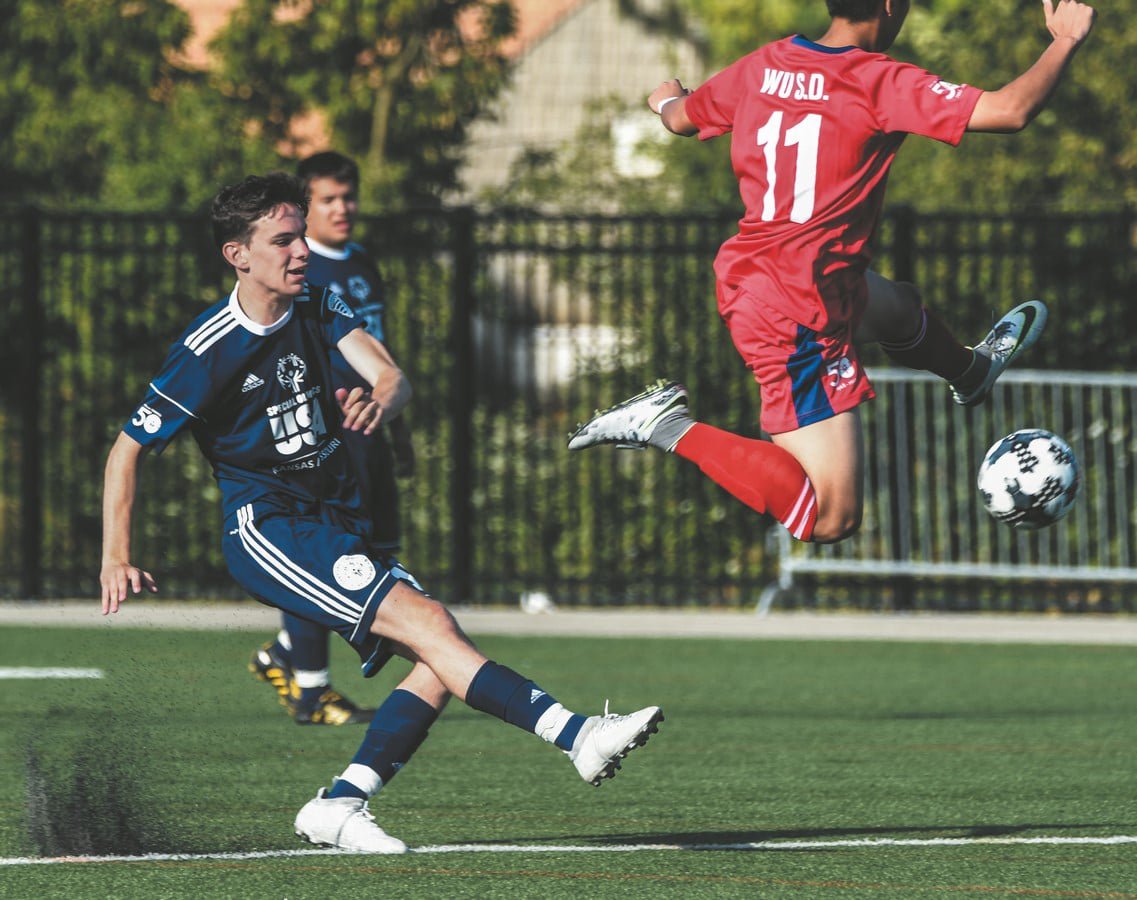 A soccer athlete follows through after kicking the ball past a jumping defender streaking through the air