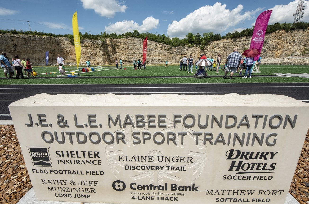 A group of athletes and volunteers play on the turf field at the Training for Life Campus