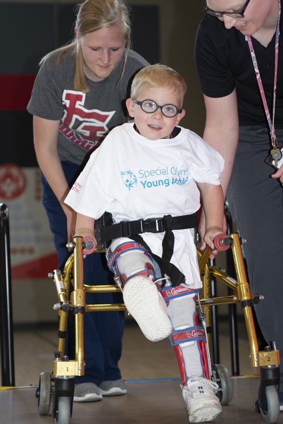 A Young Athlete uses a walker and the help of two volunteers to walk across a stage
