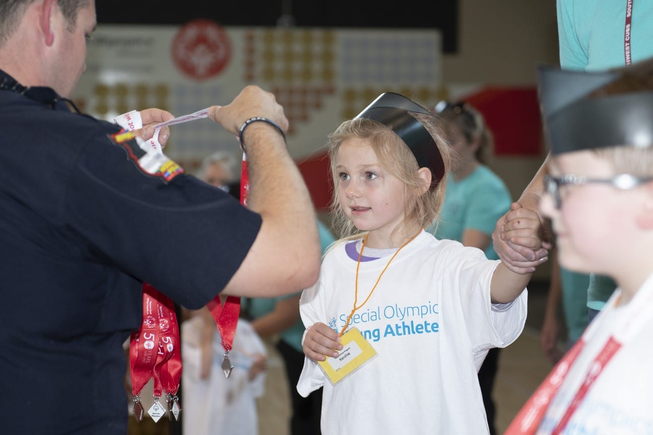 A Young Athlete wearing a paper graduation cap smiles as a police officer prepares to put a medal around their neck