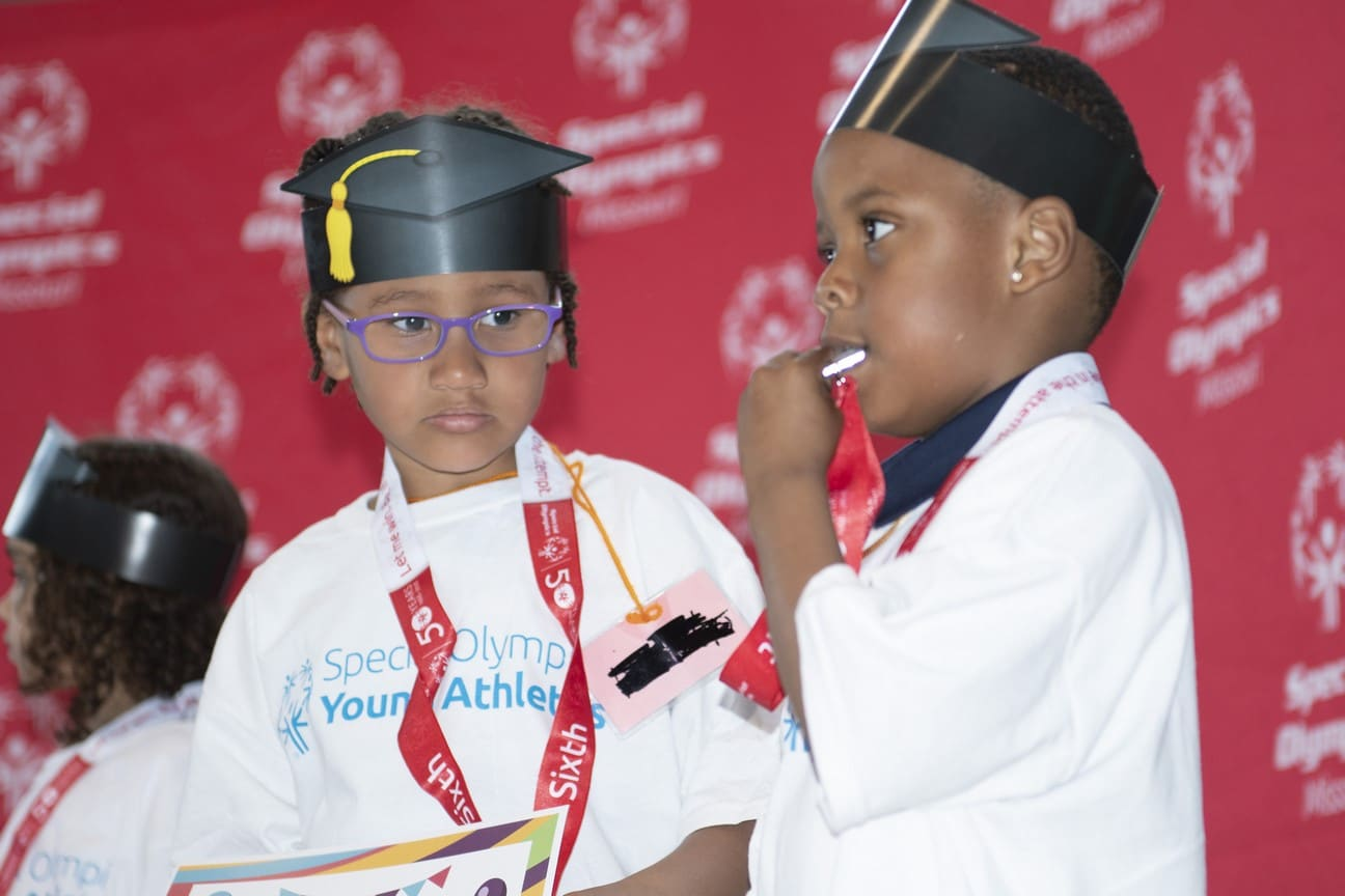 Two Young Athletes wear paper graduation caps