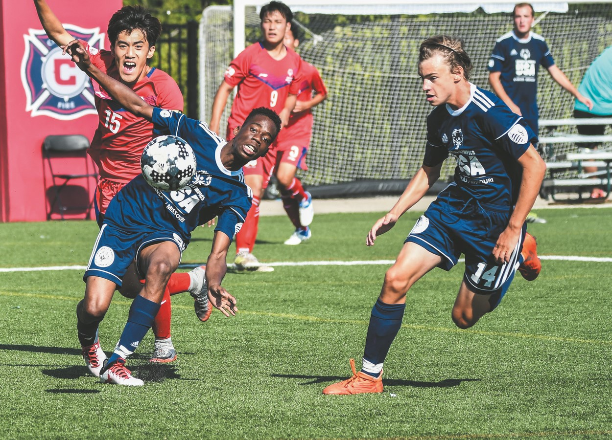Two soccer athletes strain to track down the ball while a defender tries to chase them down