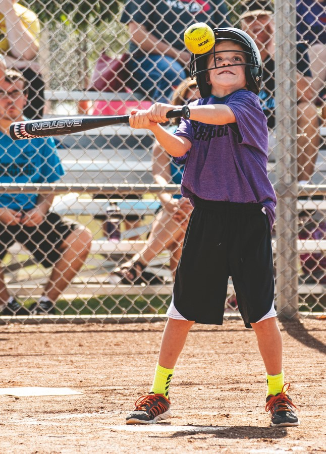 A young softball athlete primes their swing at the ball as it passes by them