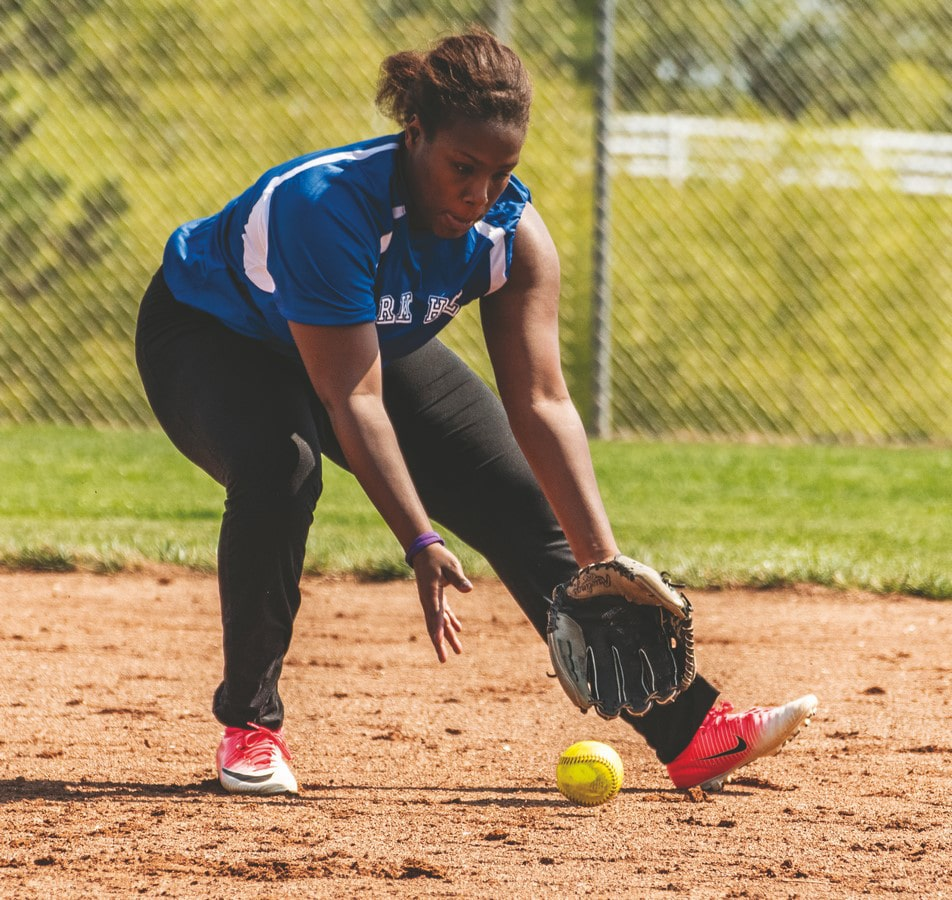 An athlete from Park Hill fields a softball moving from their right to left