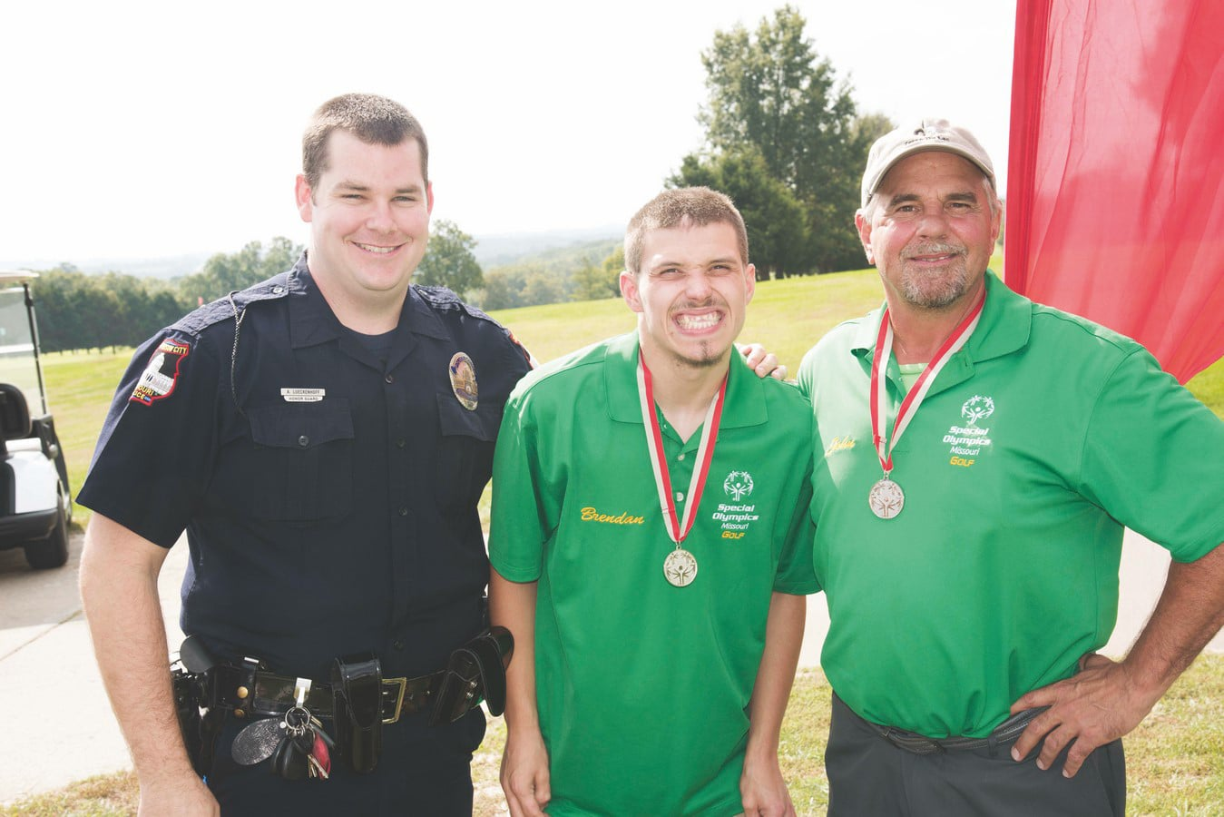 Athletes withmedals around theirs necks smile at the camera while posing with police officer