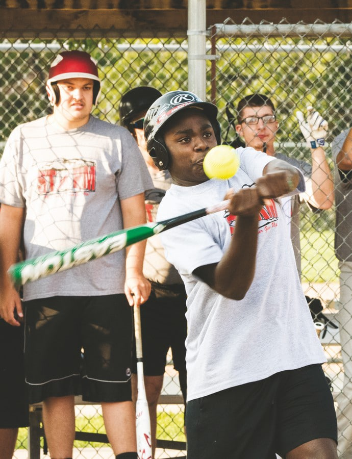 A softball athlete swings at the ball while their teammates look on from the dugout in the distance behind them