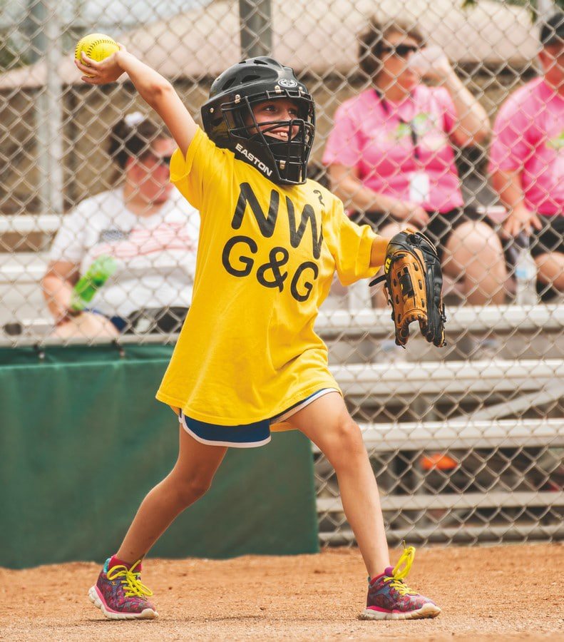 A young athlete playing catcher throws the softball back while wearing a black catcher's mask