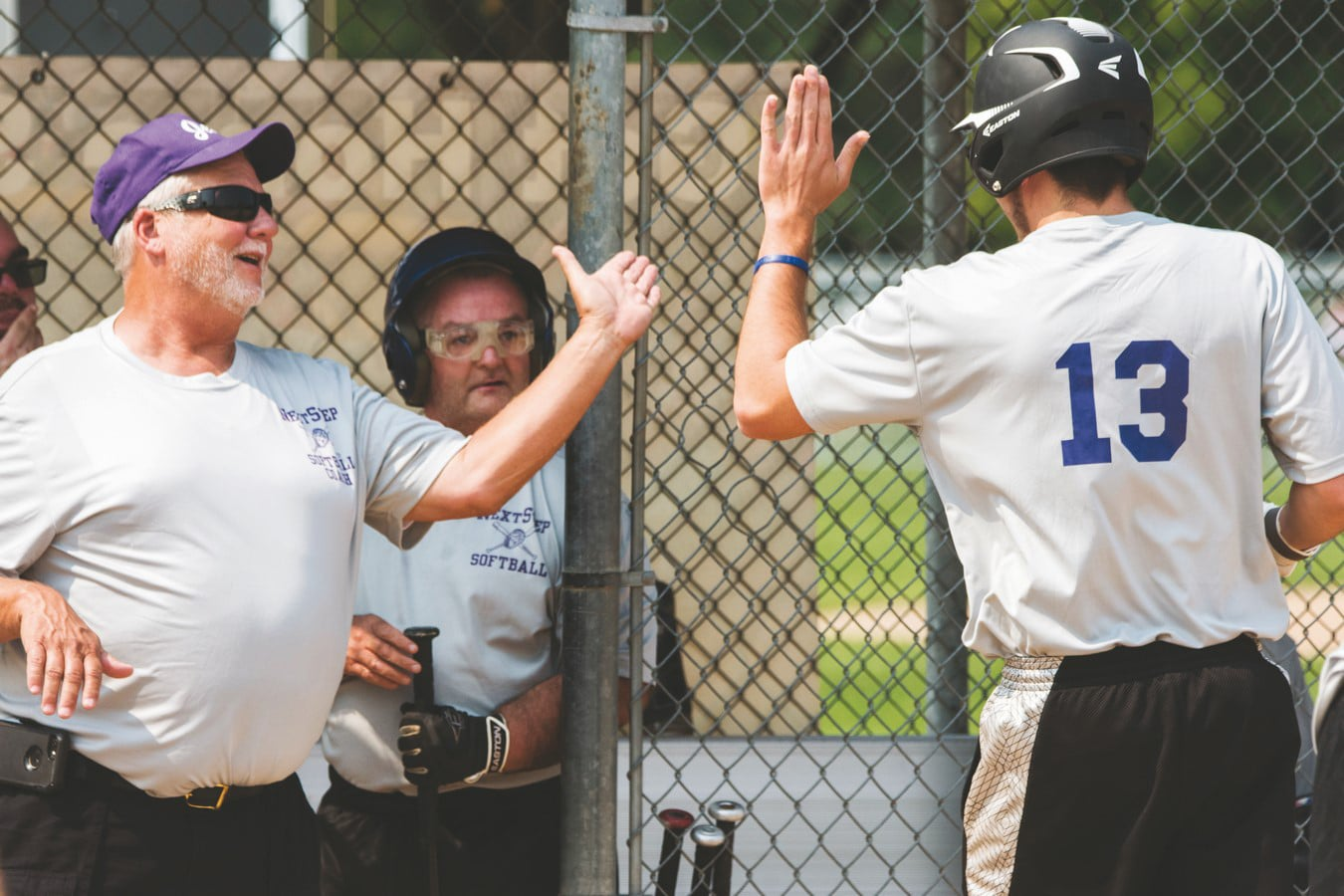 Athlete going in for a high-five with the coach standing by the dugout