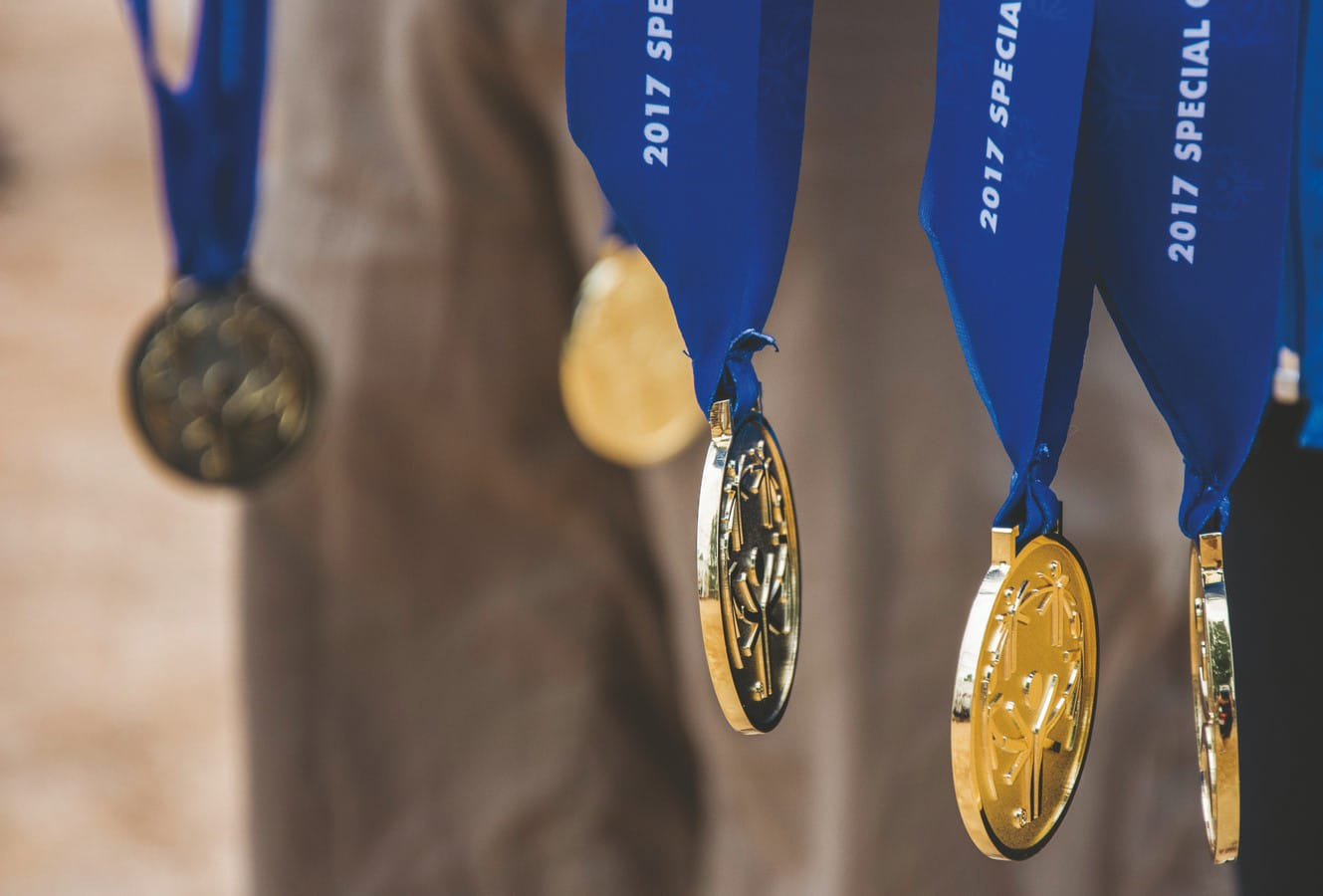 5 hanging gold medals with blue neck ribbons