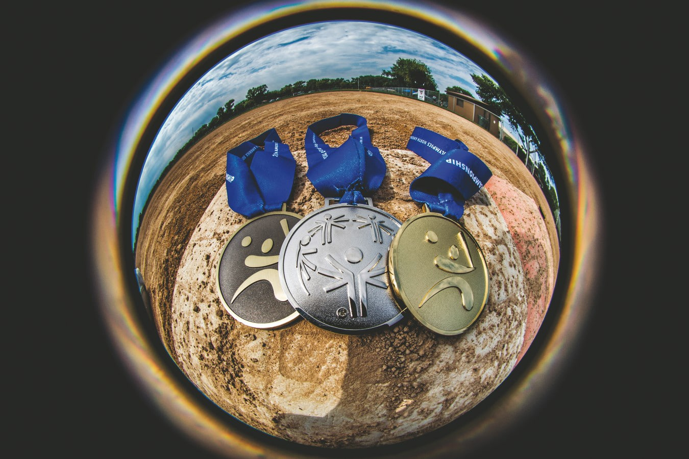 Three softball medals laying on a softball base