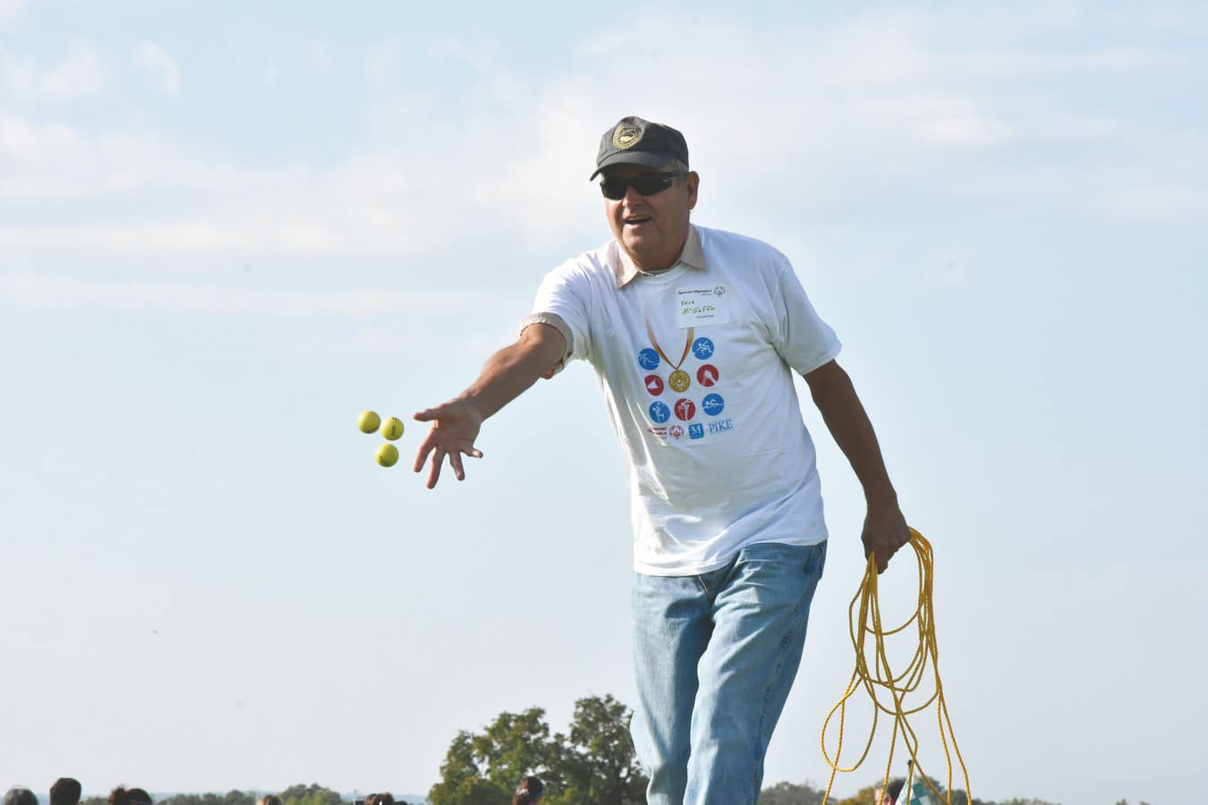 Volunteer holding a rope tosses three small yellow balls
