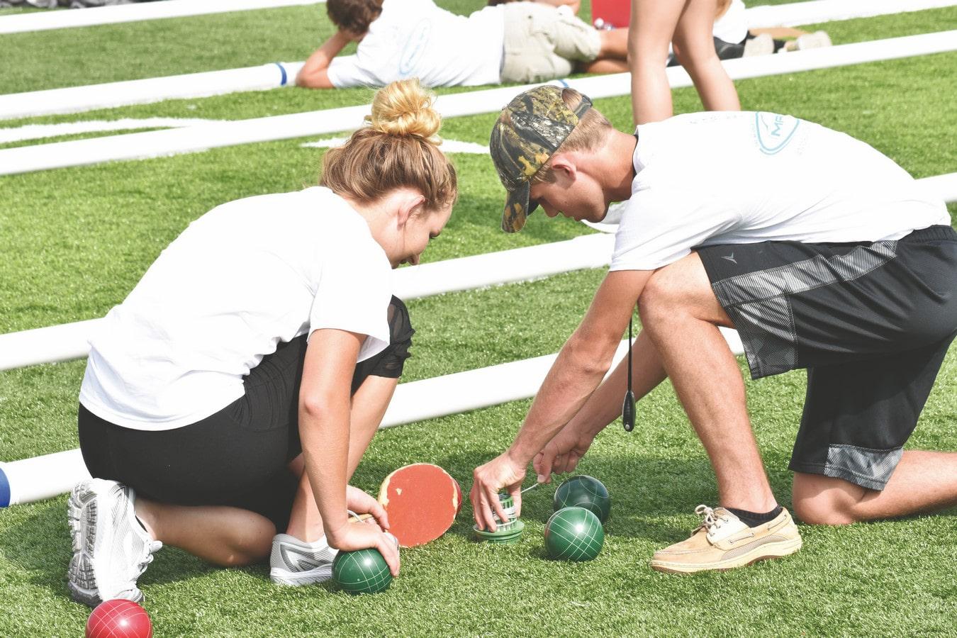 Two volunteers kneel down to measure distance of bocce balls